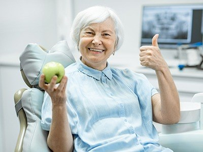 woman holding apple doing thumbs up