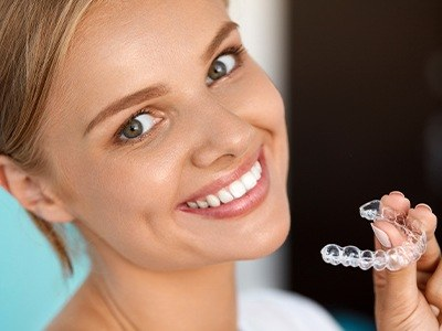 girl with perfect smile holding invisalign