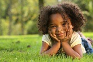 little girl hands on face smiling