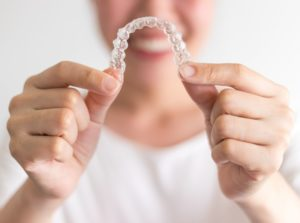 Smiling woman holding Invisalign aligner out in front of her